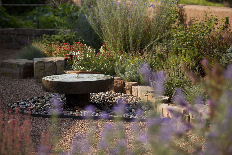 Millstone fountain integrated into garden design